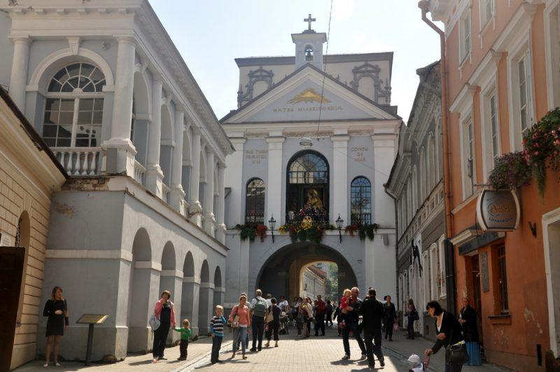 """Ostra Brama, wzniesiona w latach 1503 - 1522 w stylu gotyckim, stanowiła fragment muru obronnego. Zwana też Barmą Miednicką. Po upadku powstania styczniowego polski napis nad bramą: """"Matko Miłosierdzia pod Twoją obronę uciekamy się"""" zmieniono na łaciński: """"MATER MISERICORDIAE, SUB TUUM PRAESIDIUM CONFUGIMUS""""."""